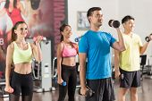 Fit handsome man smiling while exercising alternate bicep curls with dumbbells during group workout  poster