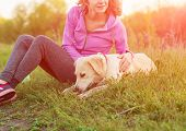 Relaxed Fitness Woman Sitting With A Playful Young Dog Golden Retriever poster