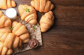 Tasty croissants, glass of milk and chocolate paste on table poster