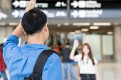 Asian Couple Say Hi Or Goodbye For Abroad At Airport. Back Asian Man Waving Hand Goodbye Girlfriend. poster