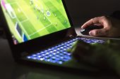 Young Man Playing Soccer Or Football Game Online With Laptop In Dark Or Late At Night. Competitive V poster