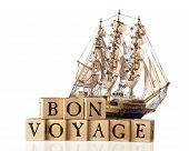 stock photo of bon voyage  - A big sailing ship behind rustic alphabet blocks arranged to say  - JPG