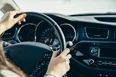 Female Hand On The Driving Wheels. Driving A Modern Car Steering Wheel And Hand Close-up. poster