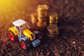 Agricultural Tractor Toy And Golden Coins On Fertile Soil Land, Income From Activity In Agriculture  poster