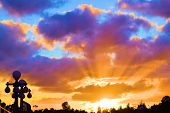 Colorful Sunset With Sunrays Shining On Clouds Taken Over A City Street poster