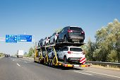 Big Car Carrier Trailer With New Cars For Sale On Bunk Platform. Car Transport Truck On The Highway poster