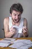 Angry Young Man Tearing His Bills, Furious With The Government And Electricity Companies poster