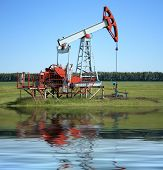 stock photo of nonrenewable  - Oil Pump Jack near a sea pumps petroleum - JPG