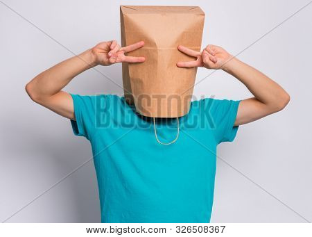 poster of Portrait of teen boy with paper bag over head making Victory gesture. Teenager cover head with bag s