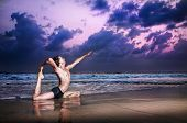 stock photo of raja  - Yoga raja kapotasana pigeon pose by man on the beach in the evening at ocean background - JPG