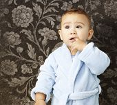 foto of housecoat  - portrait of an adorable infant with his finger in his mouth wearing a bathrobe against a vintage background - JPG