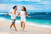 Happy Family On Honeymoon Holiday - Just Married Young Couple Having Fun, Run By Water Edge Along Se poster