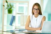 stock photo of secretary  - Portrait of a pretty secretary sitting at her desk and smiling - JPG