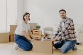 Positive Happy Husband And Wife Stand On Knees Near Carton Box With Cute Dog, Enjoy Relocation In Ne poster