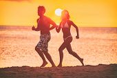 Running couple silhouettes athletes woman and man jogging together on beach training cardio outdoors poster