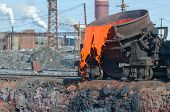 foto of slag  - The molten slag is poured from a cup on a railway platform - JPG