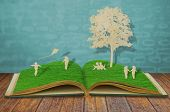 Paper cut of children play on old grass book
