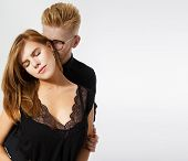 Shot Of A Fashionable Couple Hugging At Studio. Nice Elegant Couple Next To The White Background. El poster