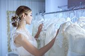 Young Beautiful Bride In A Wedding Dress Examines Wedding Dresses At The Counter In The Store. poster