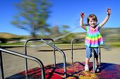 picture of merry-go-round  - Little girl playing on merri - JPG