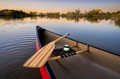 red canoe with a wooden paddle and lantern on a lake at dusk, fall scenery, wide angle view poster