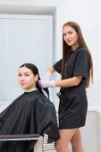 Happy Young Woman And Hairdresser. The Hairdresser Applies The Product On The Clients Long Hair poster