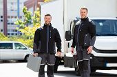 Portrait Of Smiling Two Male Electrician Carrying Tool Boxes Standing Against Truck Looking At Camer poster