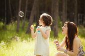 foto of little sister  - Young mother and her child playing with soap bubbles - JPG