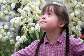 foto of playgroup  - Portrait of beautiful young girl on flowers background - JPG