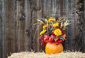 stock photo of centerpiece  - Pumpkin flower arrangement on hay against rustic wooden background - JPG