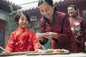 stock photo of medium-  length hair  - Mother and daughter making dumplings in traditional clothing - JPG