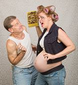stock photo of hillbilly  - Angry pregnant hillbilly woman yelling at man with chocolate - JPG