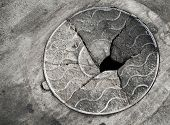 foto of manhole  - Old broken manhole cover on the asphalt road - JPG