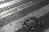 stock photo of cross-hatch  - Sewer manhole cover on asphalt road with pedestrian crossing marking - JPG