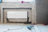 stock photo of floor heating  - Construction apartment with an installed heating and a perforator on the floor - JPG