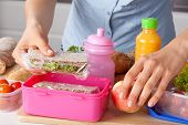 stock photo of lunch box  - Mother preparing for her children lunch box - JPG