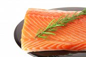 foto of fish skin  - raw fresh uncooked salmon red fish fillet on black plate with rosemary twig isolated over white background - JPG