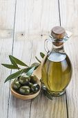 image of kalamata olives  - A glass bottle of olive oil and a wooden spoon with olives on a table - JPG