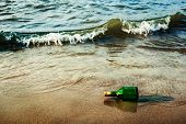 Vintage retro hipster style travel image of message bottle on beach sand in waves