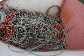 stock photo of landfill  - skeins of copper cable in a container of a landfill of waste - JPG