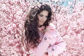 Enjoyment. Portrait Of Beautiful Woman Posing Over Pink Spring Cherry Blossoms. Spring Time.