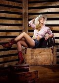Young, happy and sexy cowgirl in western style