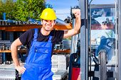 stock photo of lift truck  - builder or driver with pallet transporter or lift fork truck on construction or building site - JPG