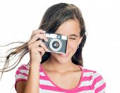 Beautiful young girl taking a picture with a vintage looking  compact camera looking through the vie