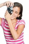 Fun happy young girl taking a photo with a vintage looking compact camera looking through the viewfi