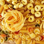 a pile of different uncooked pasta, such as tortellini, tagliatelle or penne rigate