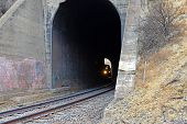 stock photo of bnsf  - The engine of a long freight train labors up the mountain and enters the dark interior of one of many tunnels heading east into the southern Sierra Nevada Range - JPG