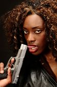 stock photo of gangsta  - A young african american female holds a semi automatic pistol during this photo shoot against black - JPG