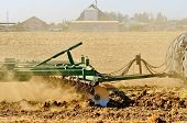 foto of cultivator-harrow  - A tractor pulls a disc harrow system implement to smooth over a dirt field in preperation for planting in central California - JPG