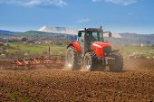 picture of tractor  - Brand new red tractor on the field working on land - JPG